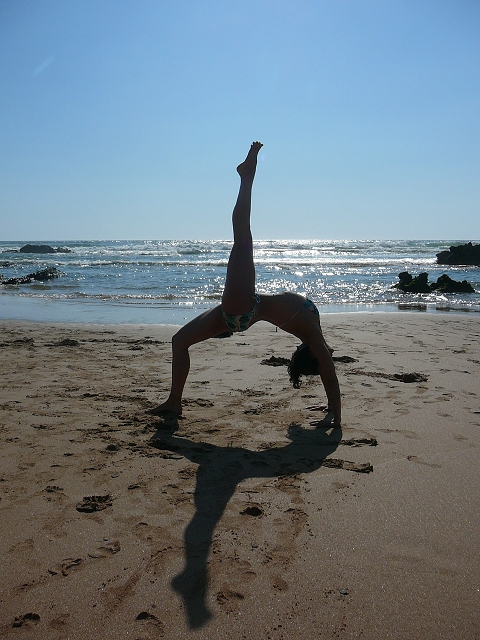 girl doing yoga on the beach during holiday