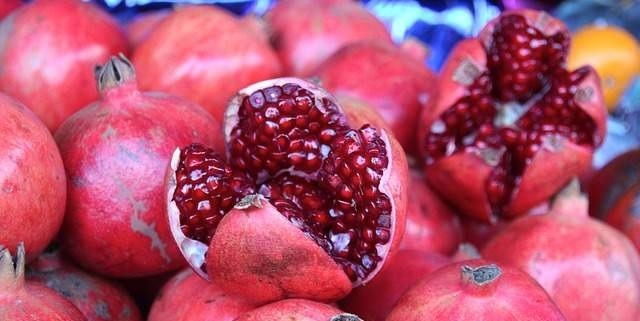 pile of pomegranate fruit with two open on top