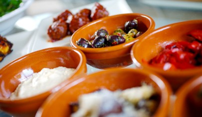 Terracotta tapas dishes holding olives, meats and cheeses