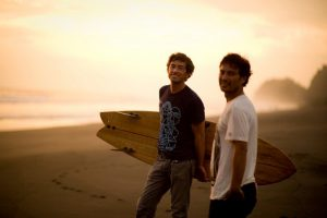two men stand on beach with surf board