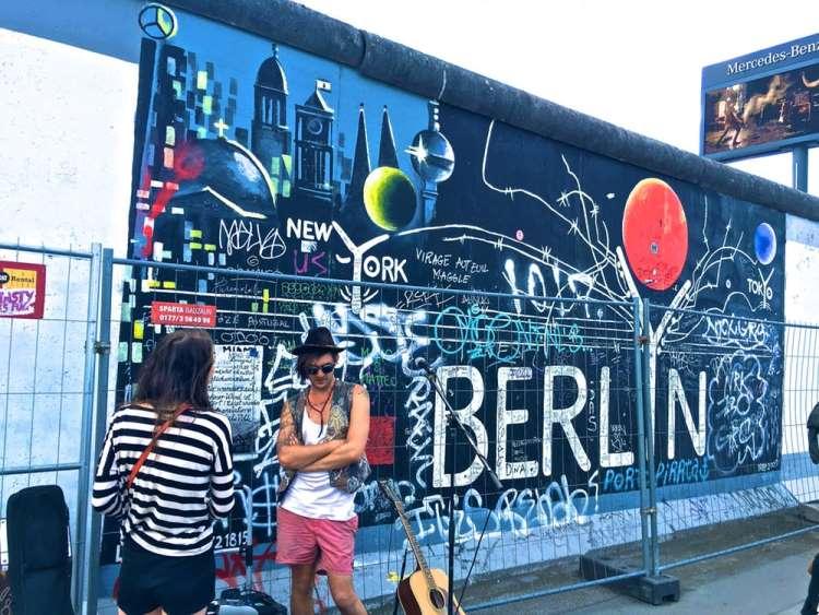 couple standing in front of street art in Berlin