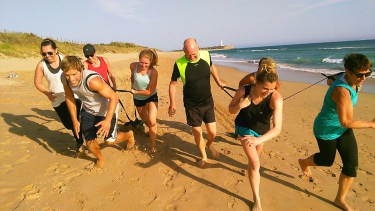 group fitness training on sandy beach in sun