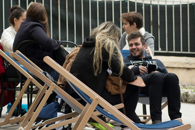 language students sitting outside on deck chairs chatting