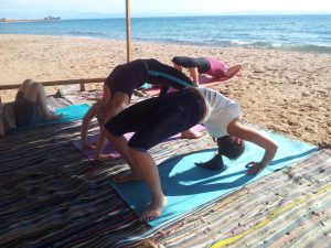 women doing yoga bridges on the beach
