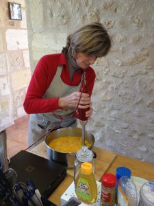 French chef blending pumpkin soup in kitchen