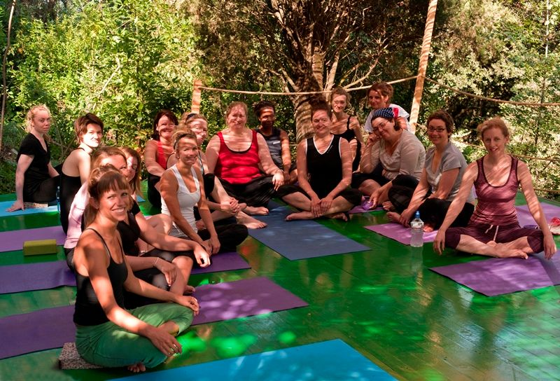 yoga students sitting together after lesson outdoors