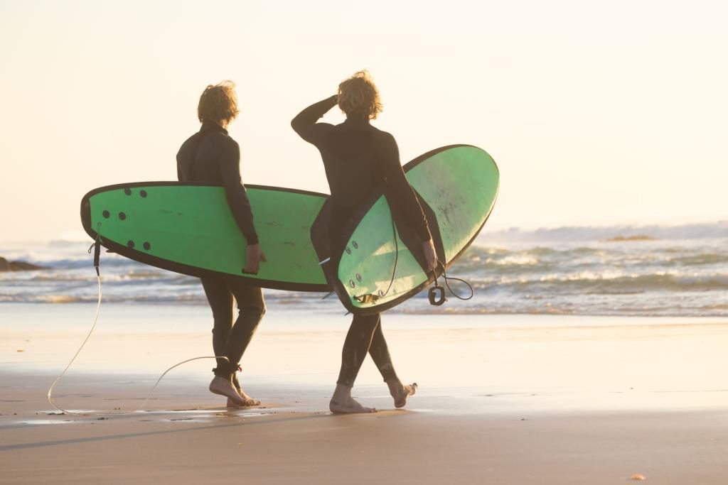 men with surfboards walking into water on beach