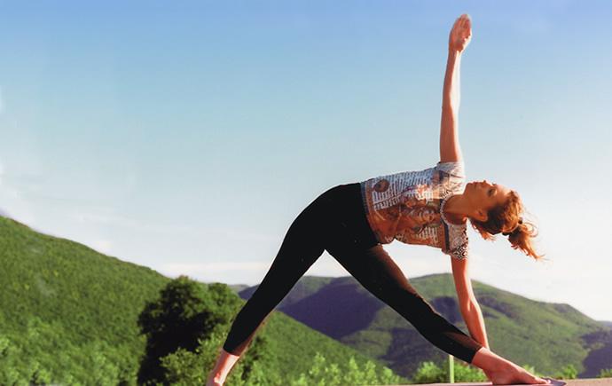 yoga triangle pose in the Italian countryside