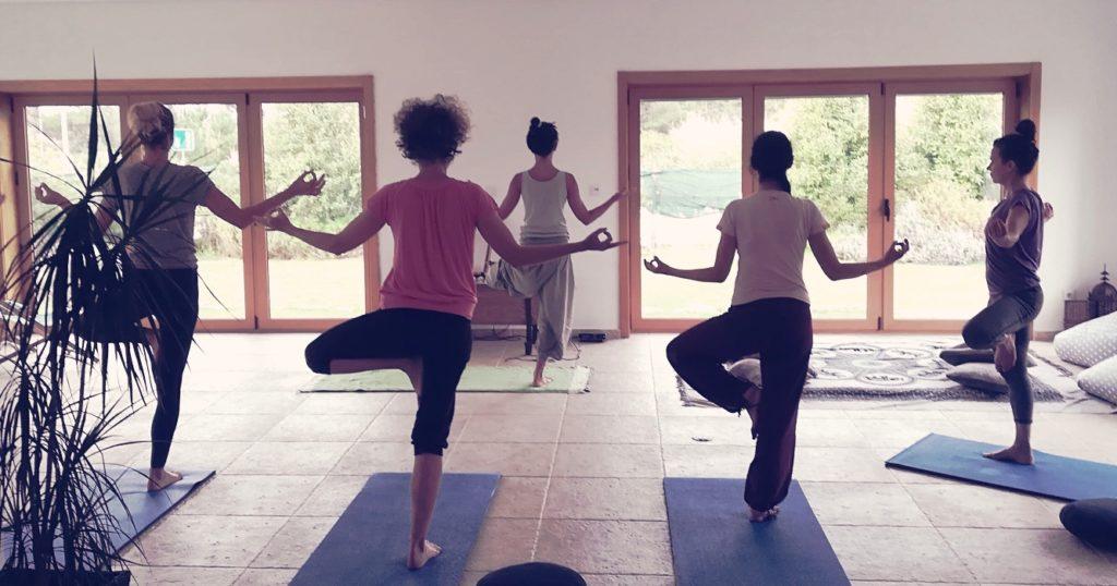 group yoga class do tree yoga pose in studio