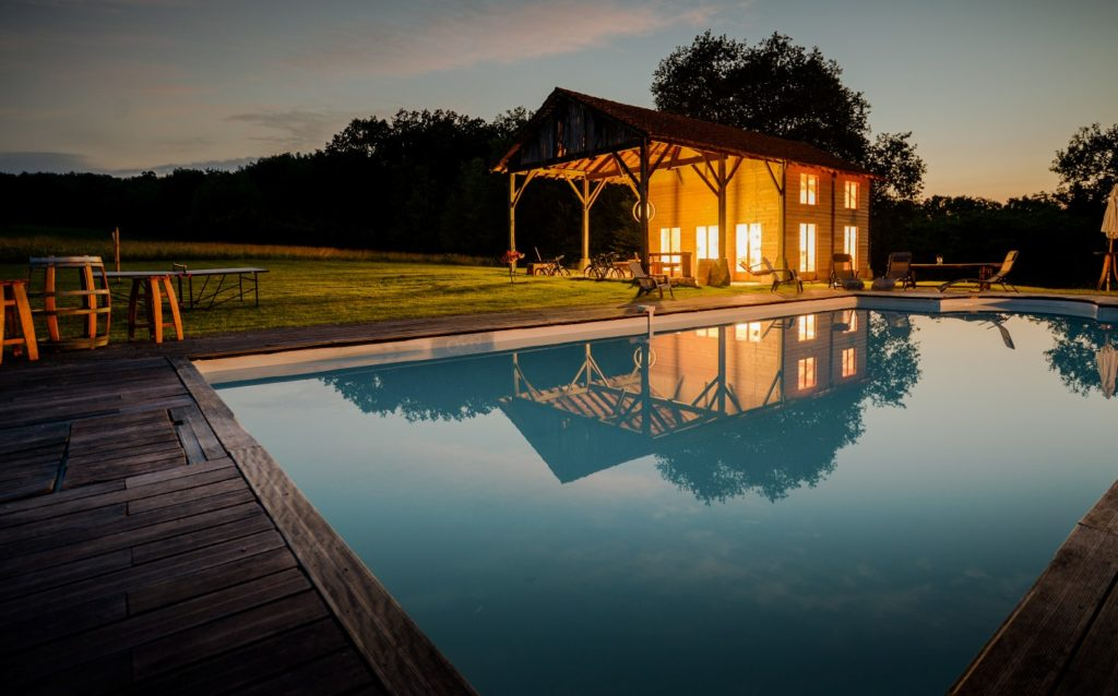 restored french barn by pool at night