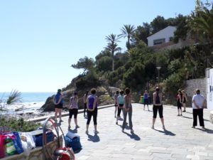 fitness group doing circuit session by the sea