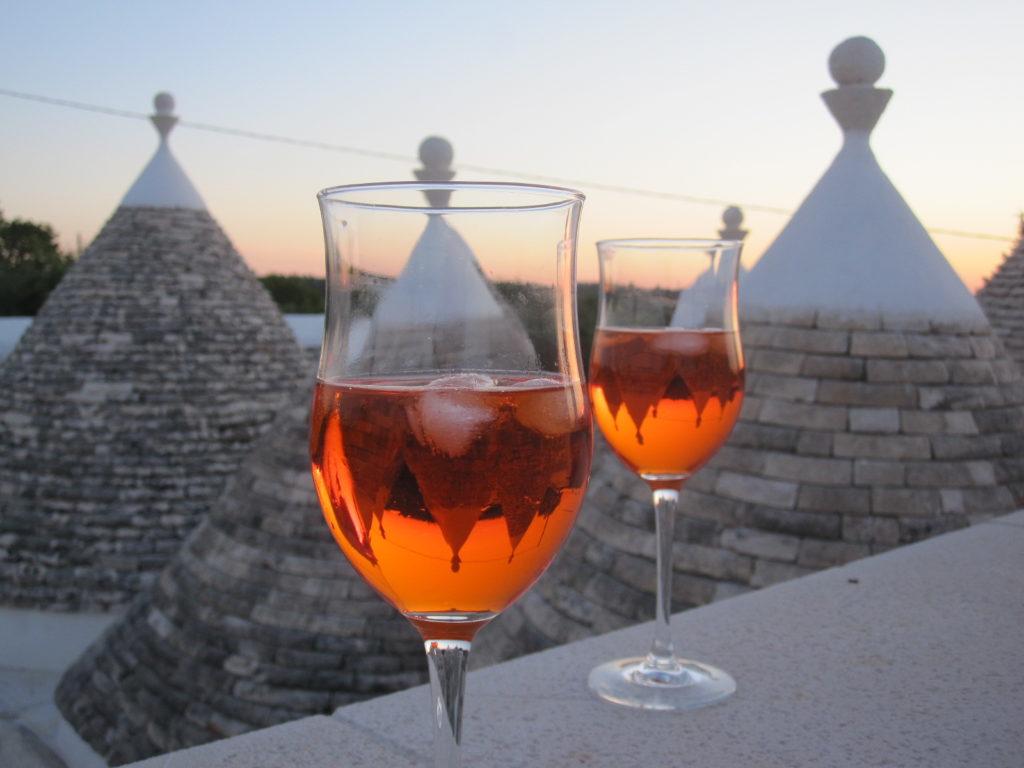 wine glasses against Alberobello in Puglia