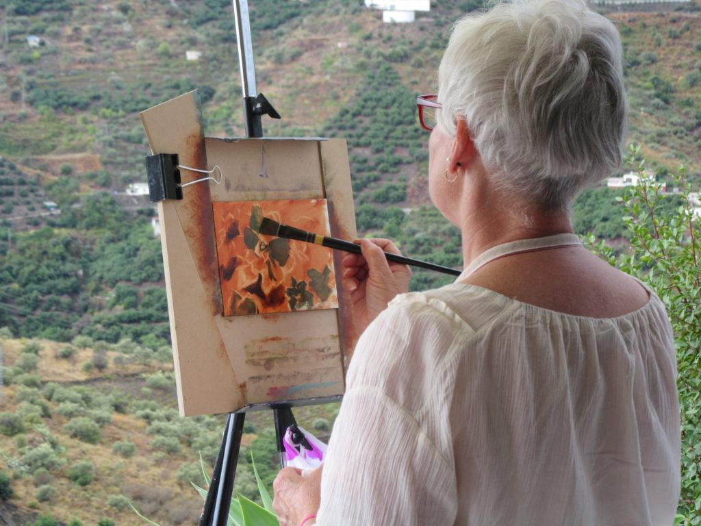 woman painting flowers against backdrop of rural Spain