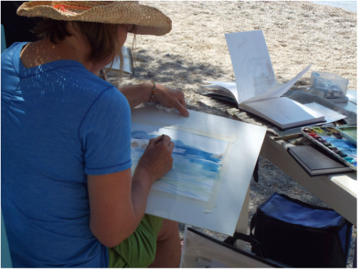 woman painting on Greek beach