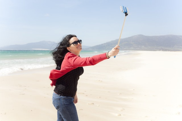 solo female traveller taking a selfie with selfie stick