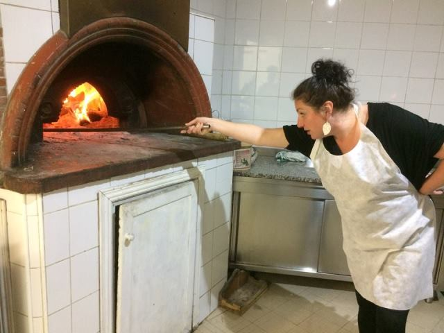 Lee putting pizza in oven on cooking holiday in Tuscany