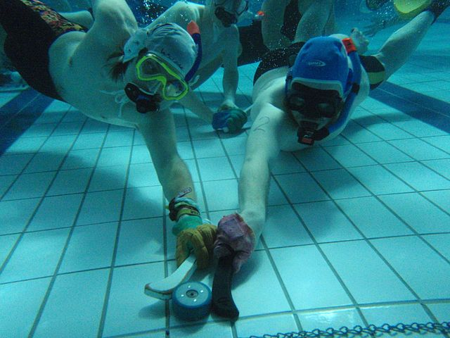 underwater hockey players fighting over puck