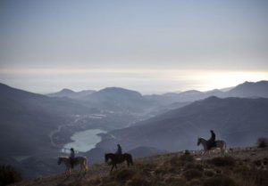 three riders shadowed against Andalucia mountains on horseback
