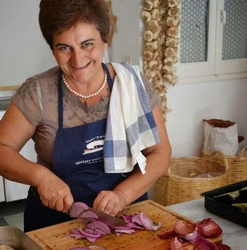 Greek cookery course host Katerina cutting onions