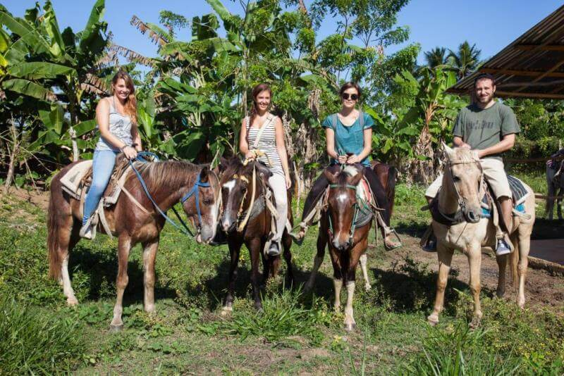 Four language holiday students on horseback in Dominican jungle