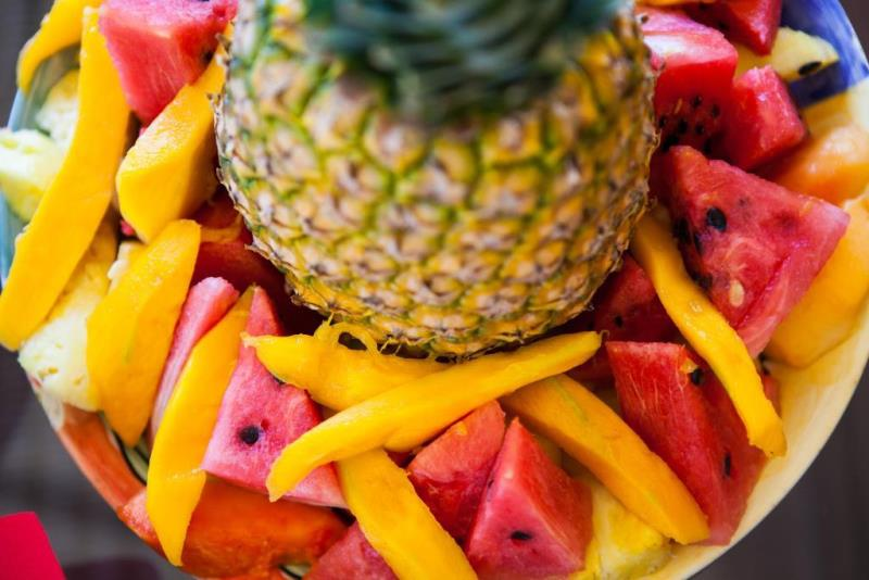 pineapple surrounded by slices of melon