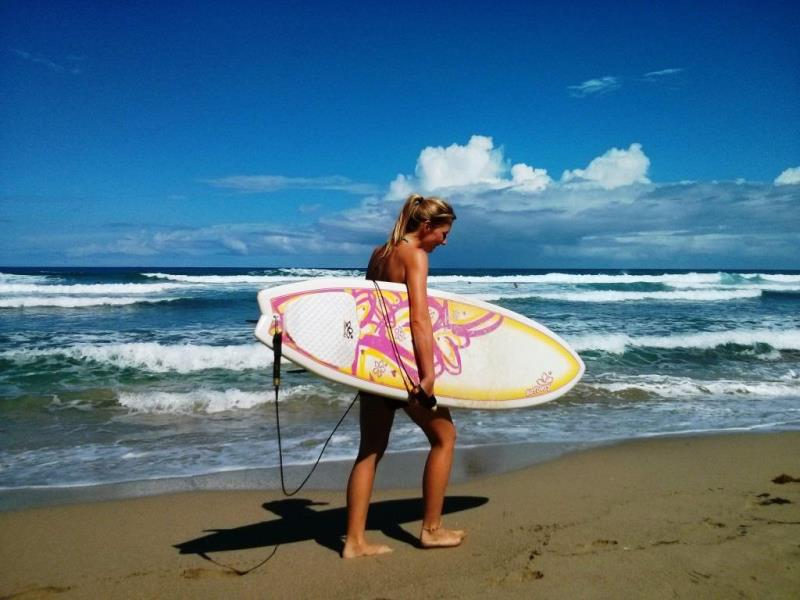 surfer girl carrying board on Dominican Republic holiday beach