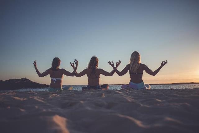 yoga women in line on beach doing lotus in Spain on holiday
