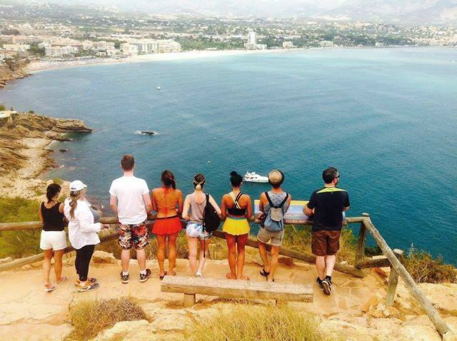 yoga and fitness holiday group standing in line looking at coast of Spain