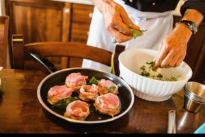 Host seasoning meat in Tuscany during cooking course