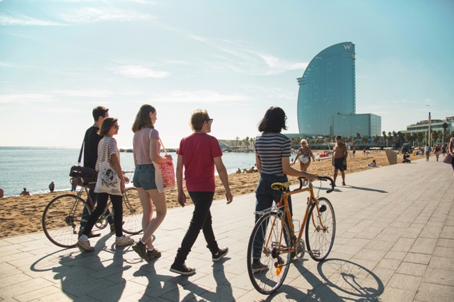 Spanish language students walking along beach promenade in Barcelona