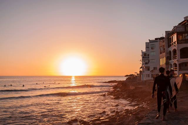 surf guys at sunset on Taghazout beach watching sunset in Morocco