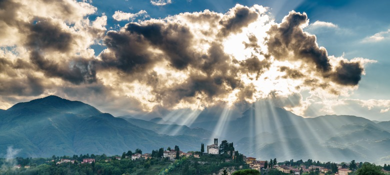 sun shining through clouds on town in Tuscany valley