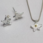 silver star necklace and pair of earrings