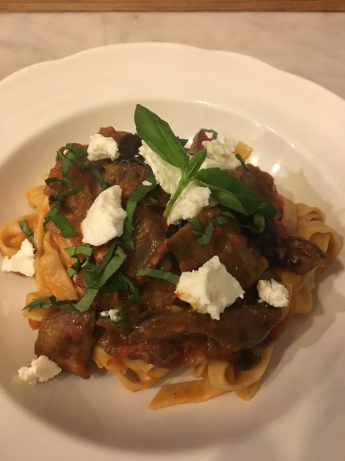 bowl of pasta alla norma with fresh ricotta on top