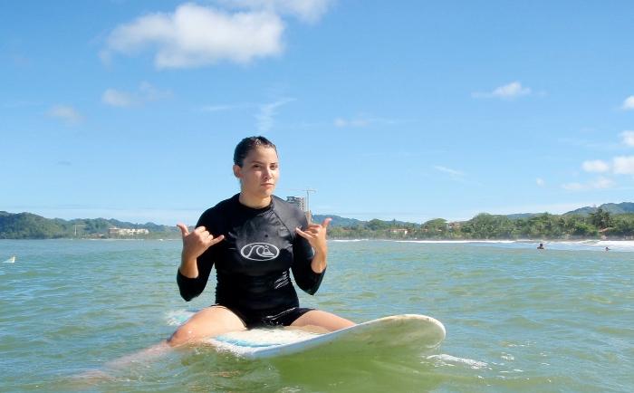 female surfer sitting on board in the ocean