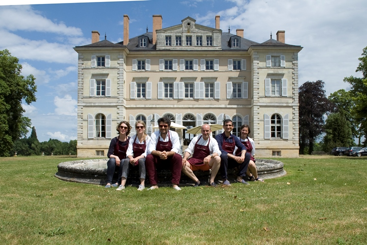 cooking guests in aprons sit outside chateau in France