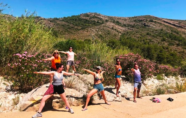fitness group do yoga pose on hike in spain