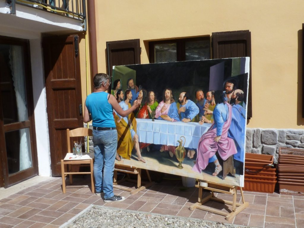 Art teacher painting The Last Supper outside in sun