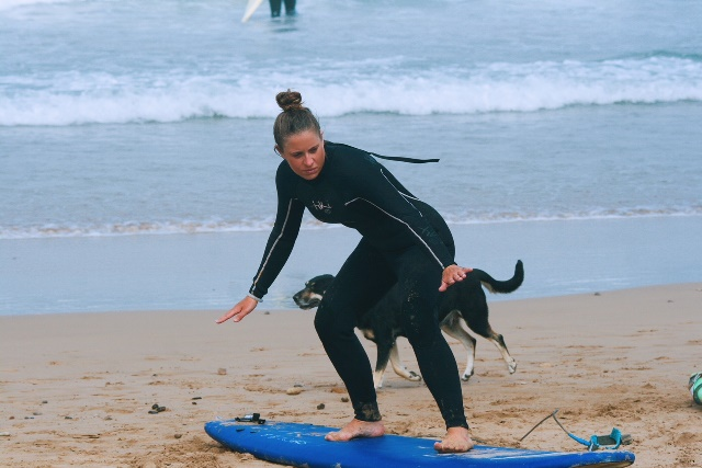 surfing woman on beach practising on board
