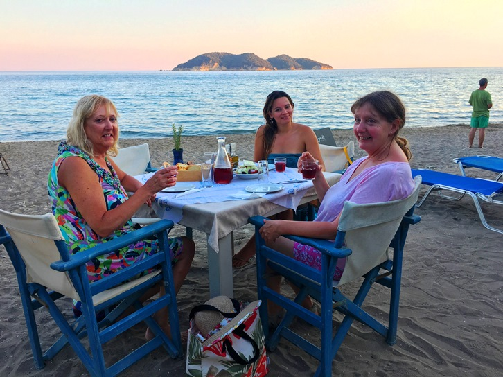 holiday makers have dinner on the beach in Greece