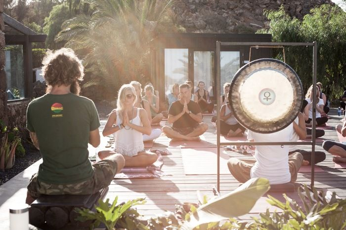 Yoga group meditate outdoors with big gong