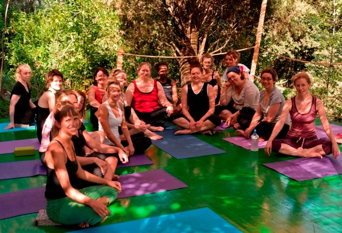 yoga group gather for photo on outdoor platform