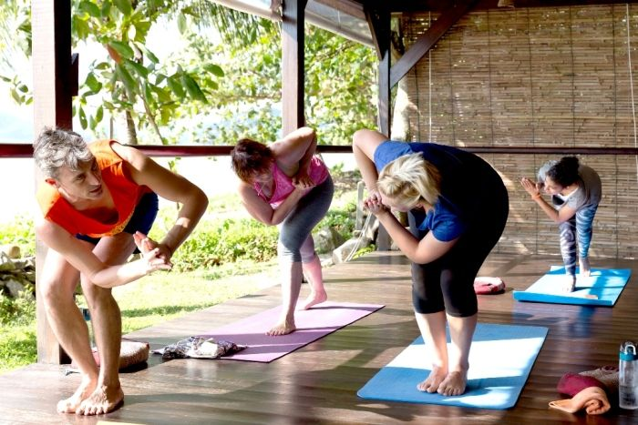 Yoga students practise yoga on outdoor platform in Thailand