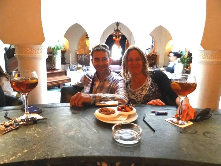 Woman and Moroccan local enjoy a drink together in bar
