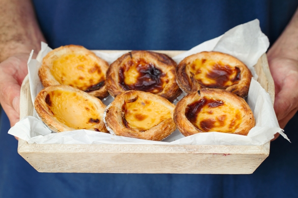 Portuguese custard tarts held in try by woman