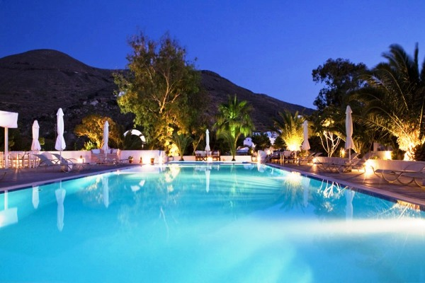 swimming pool at night surrounded by palm trees and loungers
