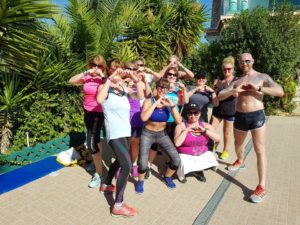 Woman fitness group pose with trainer by palm trees