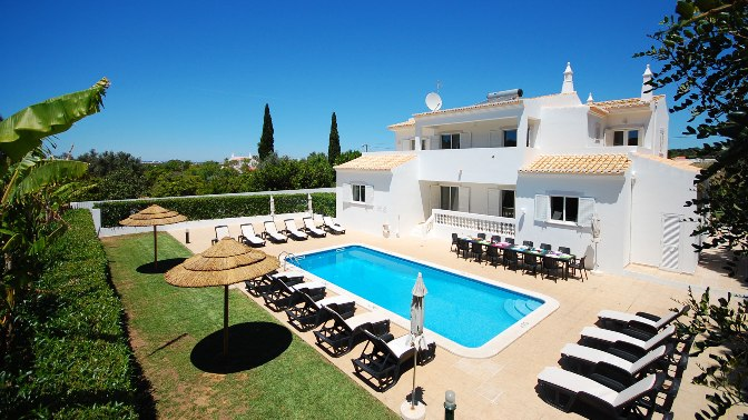 White villa with pool surrounded by loungers and umbrellas
