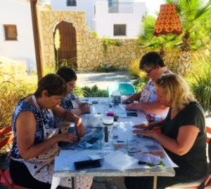 Guests doing crafts around table outside