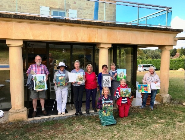 Group of painters show their work in front of house